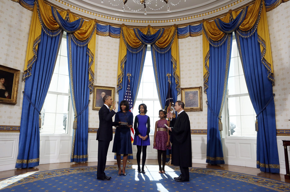 President Barack Obama is officially sworn-in by Chief Justice John Roberts in the Blue Room of the White House during the 57th Presidential Inauguration in Washington, Sunday, Jan. 20, 2013. Next to Obama are first lady Michelle Obama, holding the Robinson Family Bible, and daughters Malia and Sasha. (AP Photo/Larry Downing, Pool) ORG XMIT: WX303