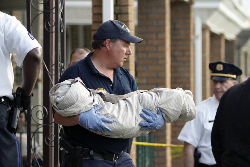 Photo -   A crime scene unit member carries a body from a home in Northeast Philadelphia on Thursday May 24, 2012, where toddler twins were found dead in their home. Police say the 18-month-old boy and girl appear to have died of suffocation and the mother is in custody. Police say their 41-year-old mother attempted to take her own life by slitting her wrists and they believe she gave some kind of prescription pills to her 4-year-old daughter. The 4-year-old girl is hospitalized. Information on her condition wasn't available. (AP Photo/Joseph Kaczmarek)