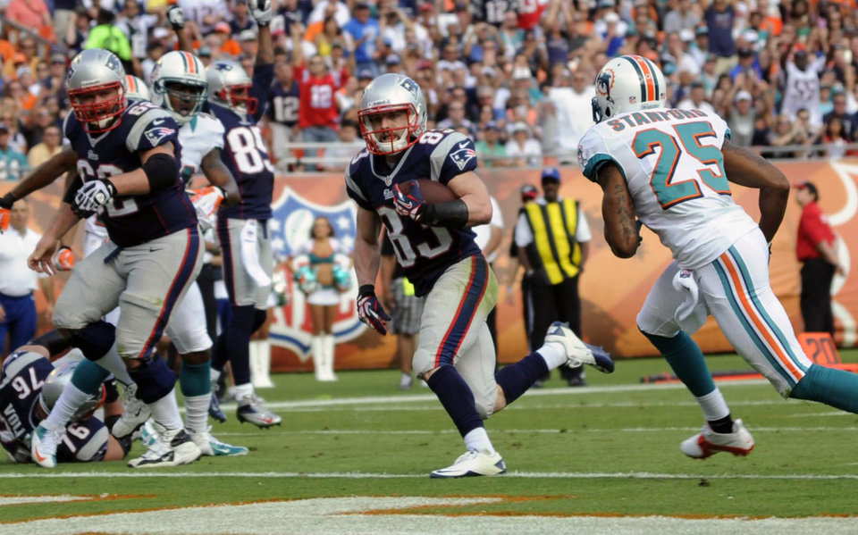 Photo - New England Patriots wide receiver Wes Welker (83) runs for a touchdown as Miami Dolphins defensive back R.J. Stanford (25) cannot catch up during the first half of an NFL football game on Sunday, Dec. 2, 2012, in Miami . (AP Photo/Rhona Wise)