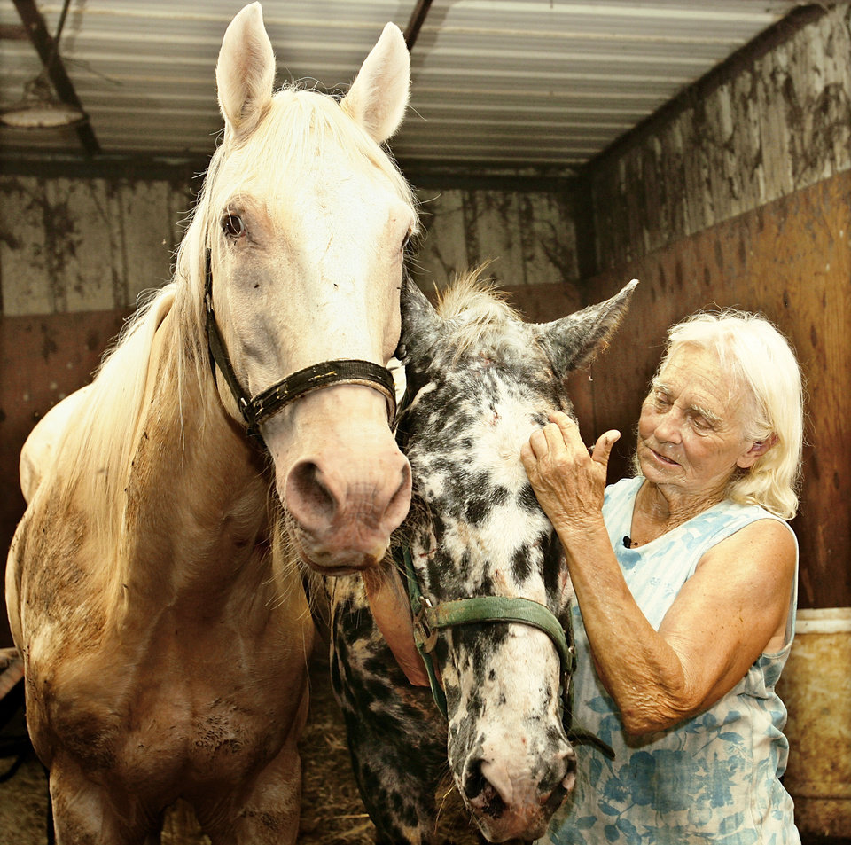 Elizabeth Munson pats a couple of blind horses, Cotton and Dallas, at Greener Pastures Horse Rescue south of Ada. The nonprofit operation must find a new home for the horses.  PHOTO BY JIM BECKEL, THE OKLAHOMAN
