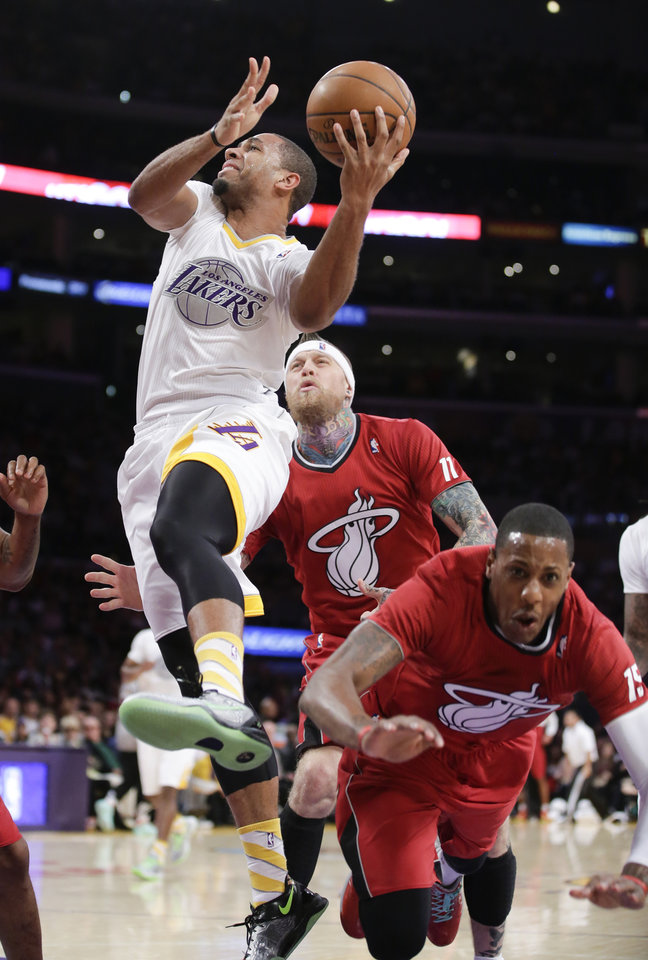 Photo - Los Angeles Lakers forward Xavier Henry, left, shoots past Miami Heat's Mario Chalmers, right, and Chris Andersen during the first half of an NBA basketball game in Los Angeles, Wednesday, Dec. 25, 2013. (AP Photo/Chris Carlson)