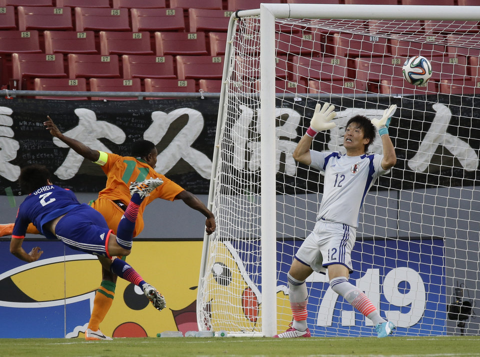 Photo - Zambia's Christopher Katongo (11) heads the ball over the arms of Japan goal keeper Shusaku Nishikawa (12) for a goal as he is defended by Japan's Atsuto Uchida (2) during the first half of an international friendly soccer match in Tampa, Fla., Friday, June 6, 2014. (AP Photo/John Raoux)