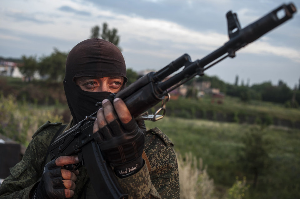 Photo - A pro-Russian fighter holds a gun during a handover of the bodies of Ukrainian troops killed in a plane shot down near Luhansk, at a check point in the village of Karlivka near Donetsk, eastern Ukraine, Wednesday, June 18, 2014. The two sides managed to arrange a brief truce Wednesday evening in the eastern town of Karlivka to allow pro-Russian forces to hand over the bodies of 49 Ukrainian troops who died when the separatists shot down a transport plane bound for the airport in Luhansk last weekend.  (AP Photo/Evgeniy Maloletka)