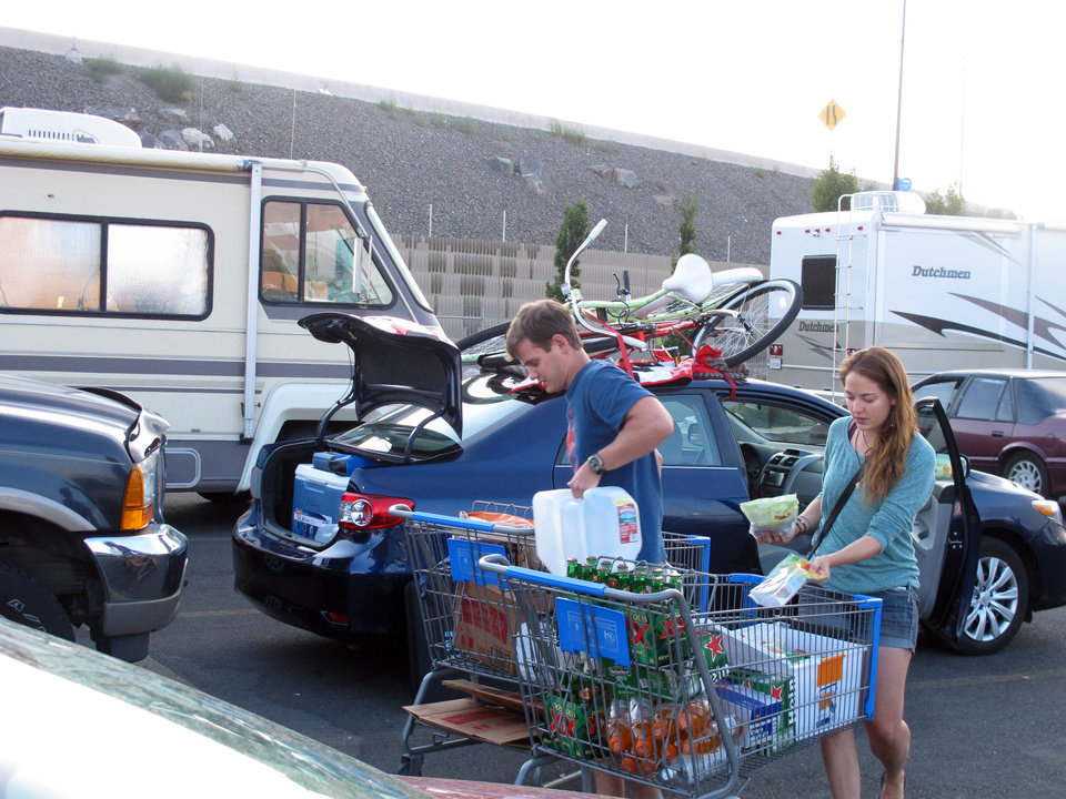 Photo - Jeff Difabrizio, left, and Jahliele Paquin of Yellowknife, Canada, load up provisions in the parking lot of a Wal-Mart, Monday, Aug. 25, 2014, in Reno, Nev., on their first trek to Burning Man. More than 100 recreational vehicles camped out at the Wal-Mart and a Reno casino Monday night when a rare rain storm turned the Black Rock Desert, 90 miles north, into a muddy quagmire. Most were optimistic the access road to the counter-culture festival on an ancient lake bed would reopen on Tuesday. (AP Photo/Scott Sonner)