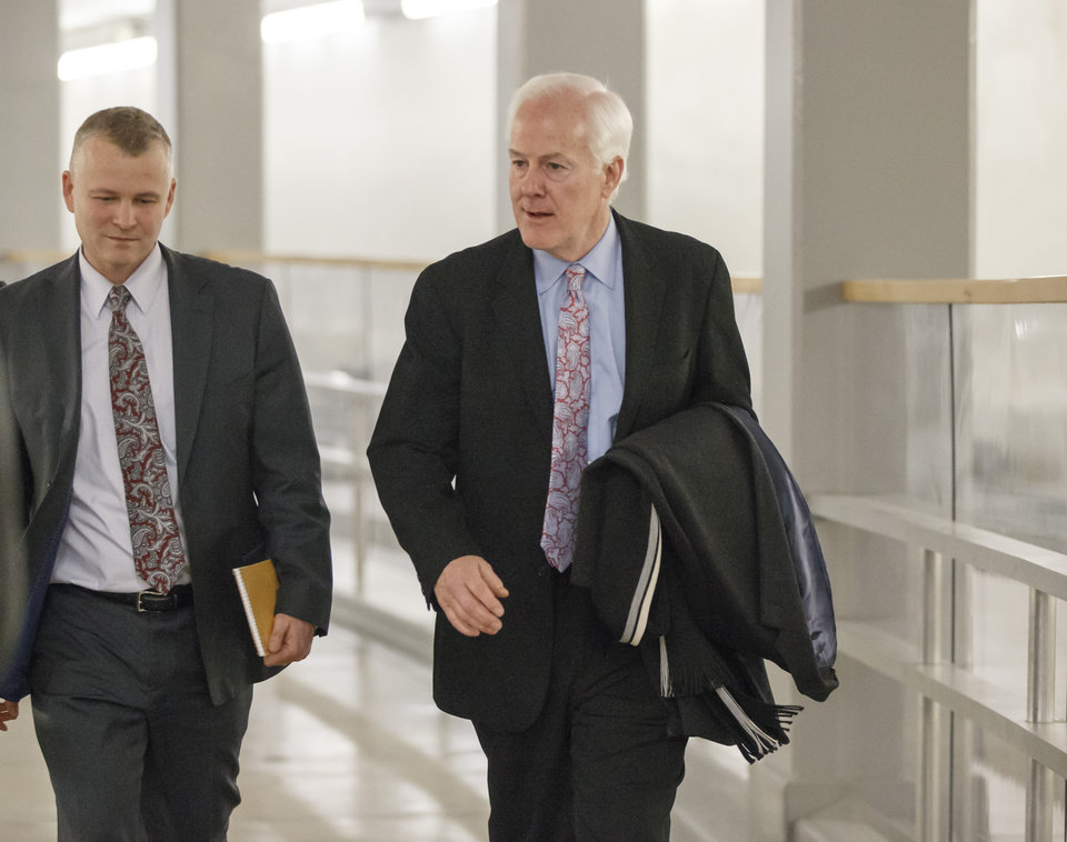 Photo - Senate Minority Whip John Cornyn, R-Texas, walks to the Senate through an underground tunnel on the way to a scheduled procedural vote in the Senate on a bill that would extend unemployment benefits, at the Capitol in Washington, Monday, Jan. 6, 2014.  (AP Photo/J. Scott Applewhite)