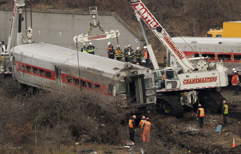 Photo - Cranes salvage the last car from from a train derailment in the Bronx section of New York, Monday, Dec. 2, 2013.  Federal authorities began righting the cars Monday morning as they started an exhaustive investigation into what caused a Metro-North commuter train rounding a riverside curve to derail, killing four people and injuring more than 60 others. A second