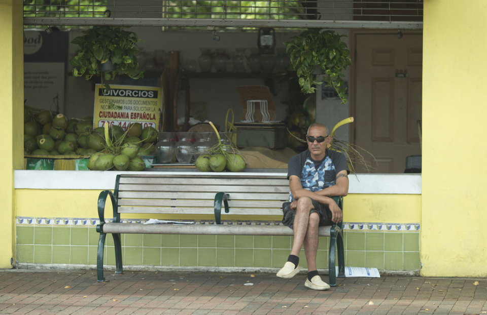 Photo - This May 2, 2014 photo shows a man sitting on a bench on Calle Ocho (Eighth Street) bench in front of the Los Pinarenos Fruteria in Miami's Little Havana. Once a refuge for Cuban exiles rekindling the tastes and sounds a lost home, today Miami's Little Havana is a mosaic of cultures and a popular tourist destination. (AP Photo/J Pat Carter)