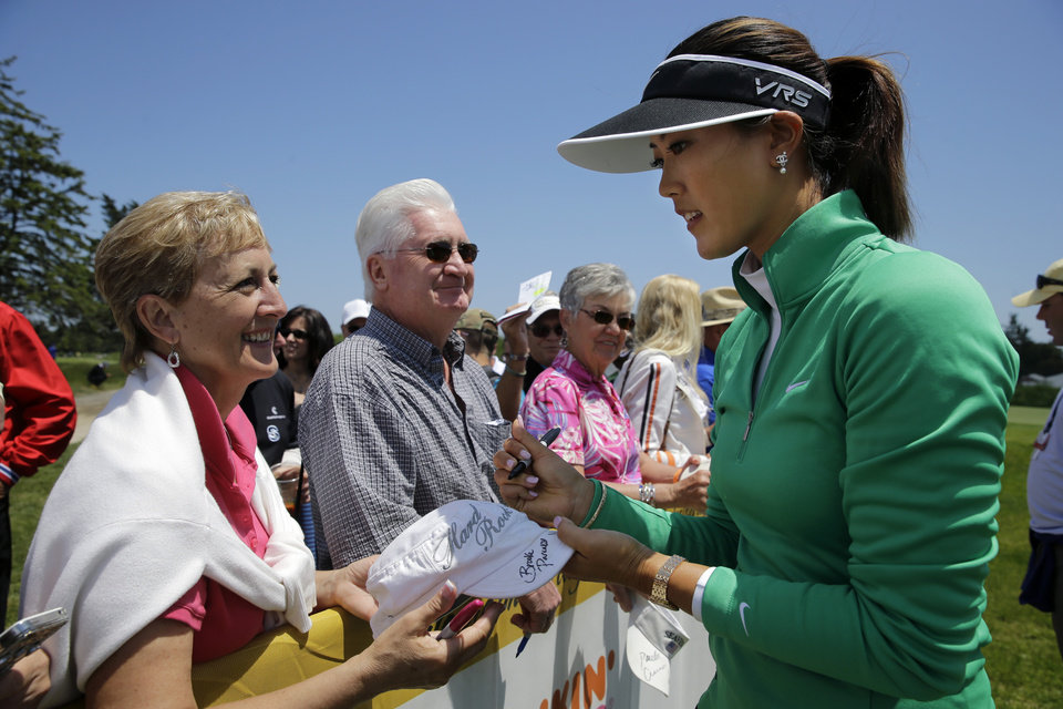 Photo - Michelle Wie signs autographs after finishing the first round of the ShopRite LPGA Classic golf tournament in Galloway Township, N.J., Friday, May 30, 2014. Wie finished 4 under par for the day. (AP Photo/Mel Evans)