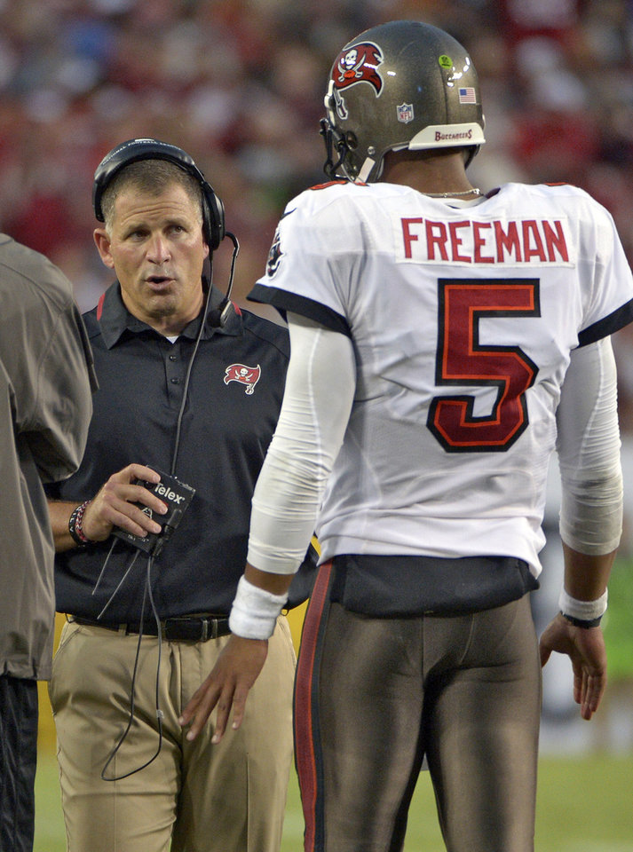 Photo - ADVANCE FOR WEEKEND EDITIONS, OCT. 5-6 - FILE - In this Sept. 15, 2013, file photo, Tampa Bay Buccaneers head coach Greg Schiano, left, talks to quarterback Josh Freeman (5) during the second quarter of an NFL football game against the New Orleans Saints in Tampa, Fla. The winless Buccaneers are in disarray, and it'll take more than a bye week to fix the mess. (AP Photo/Phelan M. Ebenhack, File)