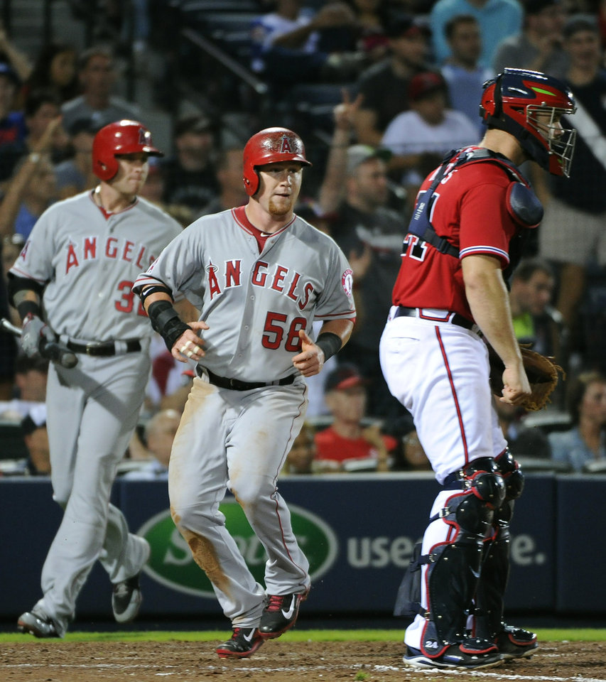 Photo - Los Angeles Angels' Kole Calhoun (56) scores past Atlanta Braves catcher Evan Gattis, right, on an RBI-single by teammate Albert Pujols during the eighth inning of a baseball game on Friday, June 13, 2014, in Atlanta. (AP Photo/David Tulis)