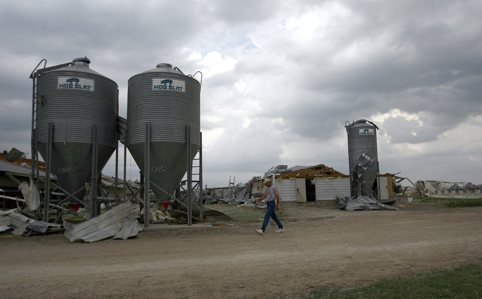 A worker walks in front of damage at the Farm 62 of Seaboard Foods near Lacey, Okla., Saturday, May 24, 2008. The farm was severely damaged by a tornado. BY SARAH PHIPPS, THE OKLAHOMAN
