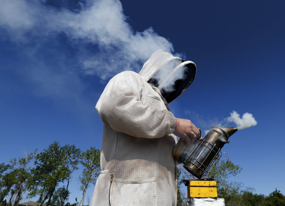 Brian Royal demonstrates bee keeping techniques to the Noble Bee Keepers Club at his home based business on Saturday, May 4, 2013, in Norman, Okla.  