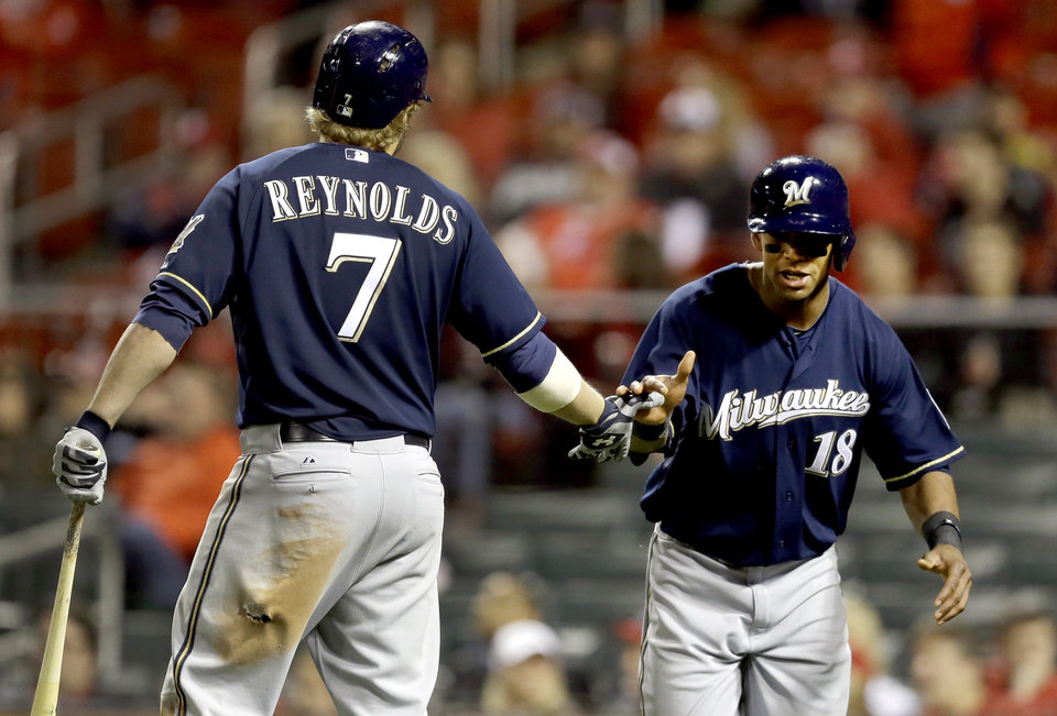Photo - Milwaukee Brewers' Khris Davis, right, is congratulated by teammate Mark Reynolds, left, after scoring on a single by Lyle Overbay during the 11th inning of a baseball game against the St. Louis Cardinals, Tuesday, April 29, 2014, in St. Louis. (AP Photo/Jeff Roberson)