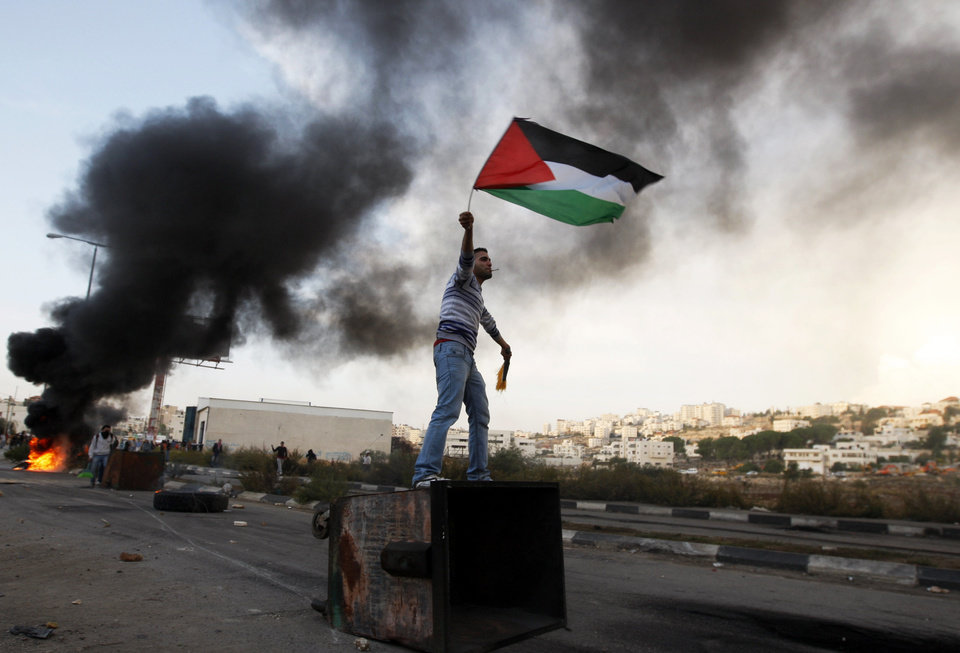 A Palestinian man waves national flag during a protest against Israel's operations in Gaza Strip, outside Ofer, an Israeli military prison near the West Bank city of Ramallah, Sunday, Nov. 18, 2012. (AP Photo/Majdi Mohammed)