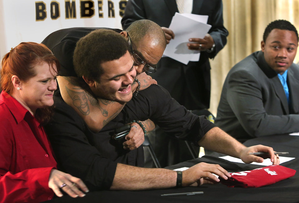 Photo - Midwest City High School offensive lineman Carlos Freeman signed his name to a letter of intent to play football at Washington State University during a signing ceremony with fellow Bomber players in the school's performing arts building on Wednesday, Feb. 6, 2013.  With Freeman are his dad, Carlos Freeman, Sr. and his mom, Kim Lowe.  Photo by Jim Beckel, The Oklahoman