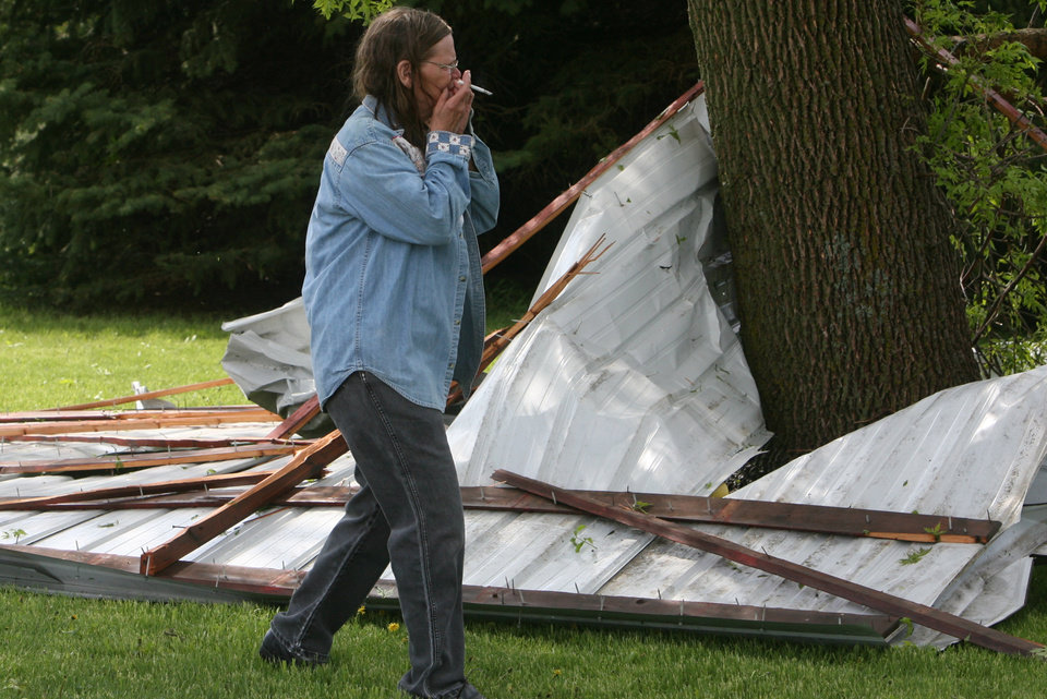 Photo - June McFarland reacts to the first sight of storm damage in rural Osage, Iowa on Sunday, May 19, 2013. A powerful weather system moved through the area on Sunday afternoon triggering tornado warnings, high winds and hail. (AP Photo/The Globe Gazette, Arian Schuessler)