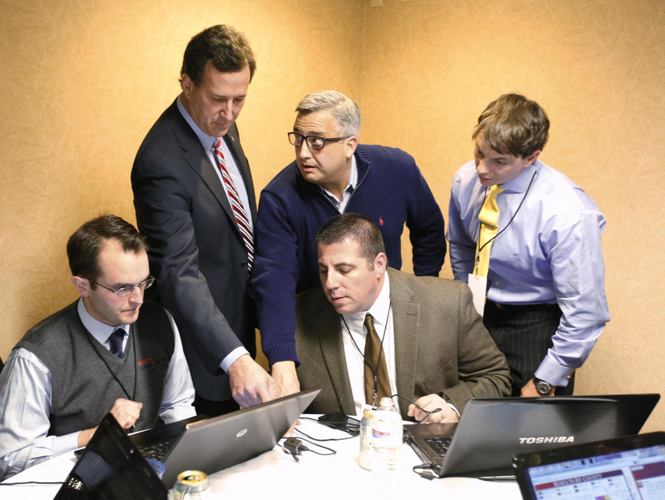 Photo -   FILE - In this Jan. 3, 2012, file photo Republican presidential candidate, former Pennsylvania Sen. Rick Santorum, top left, looks over Iowa Republican presidential caucus returns with his campaign manager, Michael Biundo, center foreground, and other campaign staff in his Iowa hotel room. Romney met privately Friday with Santorum, who has indicated he will ultimately endorse Romney. Romney has also hired Biundo, to broaden coalitions with conservative groups. (AP Photo/Charlie Riedel)