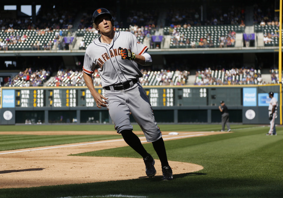 Photo - San Francisco Giants' Hunter Pence returns to the dugout after circling bases following his three-run home run against the Colorado Rockies in the first inning of a baseball game in Denver on Monday, Sept. 1, 2014. (AP Photo/David Zalubowski)