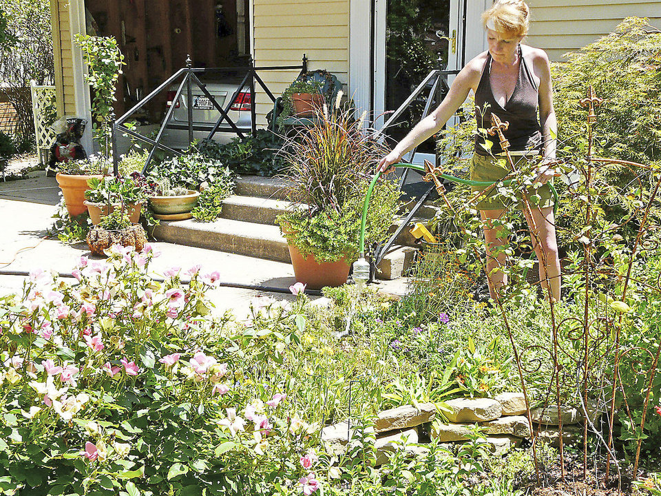 Colleen Merkle hand waters a flower garden in her front yard Saturday in the 500 block of Shawnee Street in Norman. PHOTO BY CONNIE HEFNER, FOR THE OKLAHOMAN