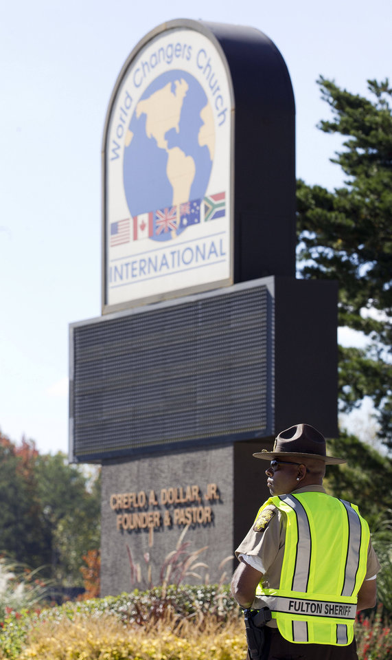 Photo -   A Fulton County Sheriff's Deputy stands guard outside the World Changers International church in College Park, Ga., after a fatal shooting inside Wednesday, Oct. 24, 2012. Police say a volunteer leading a prayer service was shot and killed by a former church employee. (AP Photo/John Bazemore)