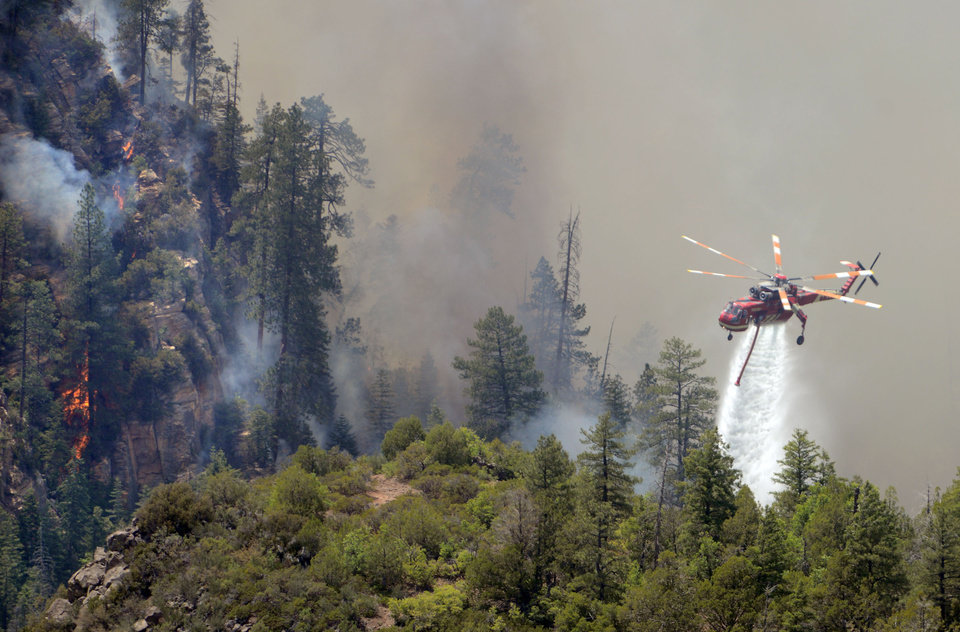 Photo - A firefighting helicopter drops water on a forest fire in Oak Creak Canyon in Sedona, Ariz., on Thursday May 22, 2014. The human-caused Slide Fire started Tuesday and had burned 7 1/2 square miles in and around Oak Creek Canyon, a scenic recreation area along a highway between Sedona and Flagstaff that normally would be teeming with tourists as the Memorial Day weekend approaches. (AP Photo/ Vyto Starinskas)