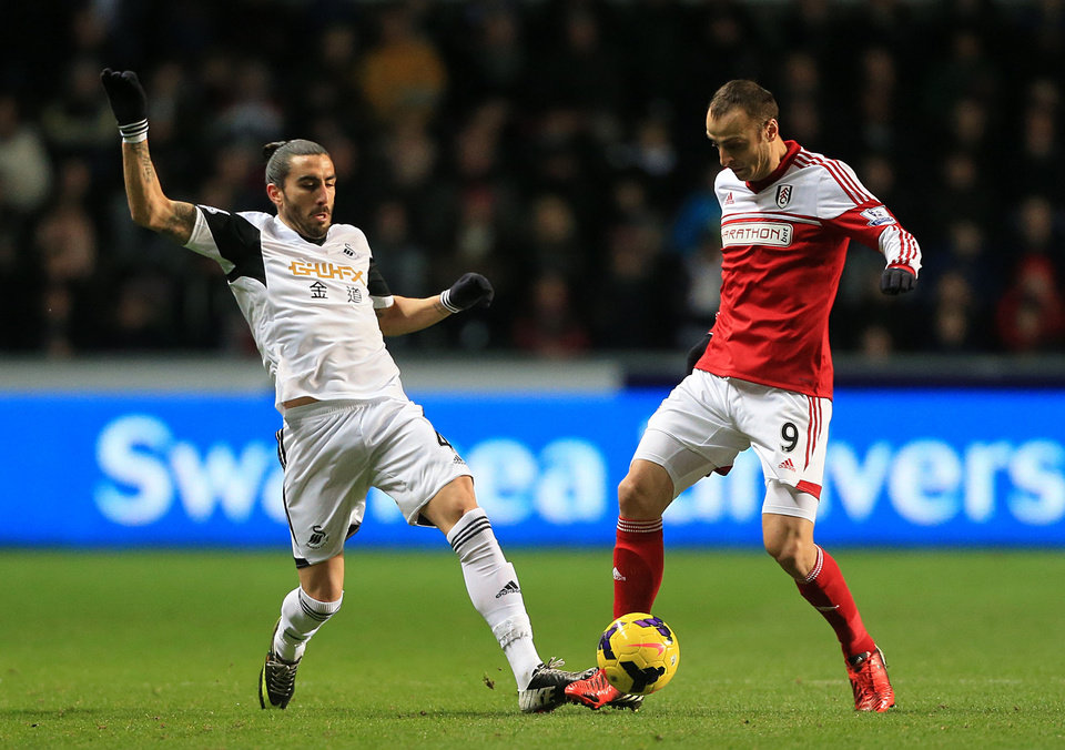 Photo - Fulham's Dimitar Berbatov, right, and Swansea City's Chico battle for the ball during their English Premier League soccer match at the Liberty Stadium, Swansea, Wales, Tuesday, Jan. 28, 2014. (AP Photo/Nick Potts, PA Wire)   UNITED KINGDOM OUT  -  NO SALES  -  NO ARCHIVES