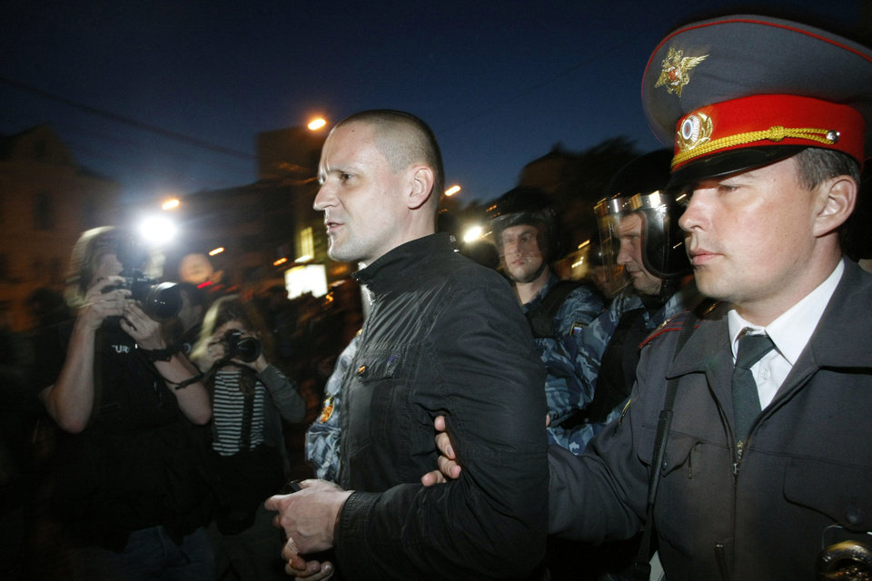 Photo -   CORRECTS SPELLING OF SERGEI - Russian police officers detain opposition leader Sergei Udaltsov while protesters gather near the presidential administrations building in downtown Moscow early Tuesday, May 8, 2012, a day after Putin's inauguration. Vladimir Putin took the oath of office in a brief but regal Kremlin ceremony on Monday, while on the streets outside thousands of helmeted riot police prevented hundreds of demonstrators from protesting his return to the presidency. (AP Photo/Alexander Zemlianichenko Jr )