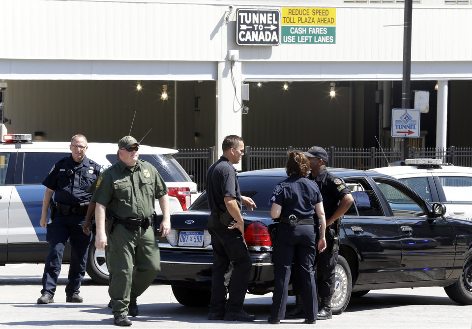 Photo -   Authorities meet during a investigation of a bomb threat at the Detroit Windsor Tunnel Thursday, July 12, 2012. The tunnel was closed to traffic after the threat was called in on the Canadian side, tunnel chief executive Neal Belitsky told The Associated Press. The call was made some time after 12:30 p.m. to the duty free shop on a plaza on the tunnel's Windsor side, tunnel executive vice president Carolyn Brown said. The underwater tunnel stretches about a mile beneath the Detroit River, which is one of North America's busiest trade crossings. (AP Photo/Paul Sancya)