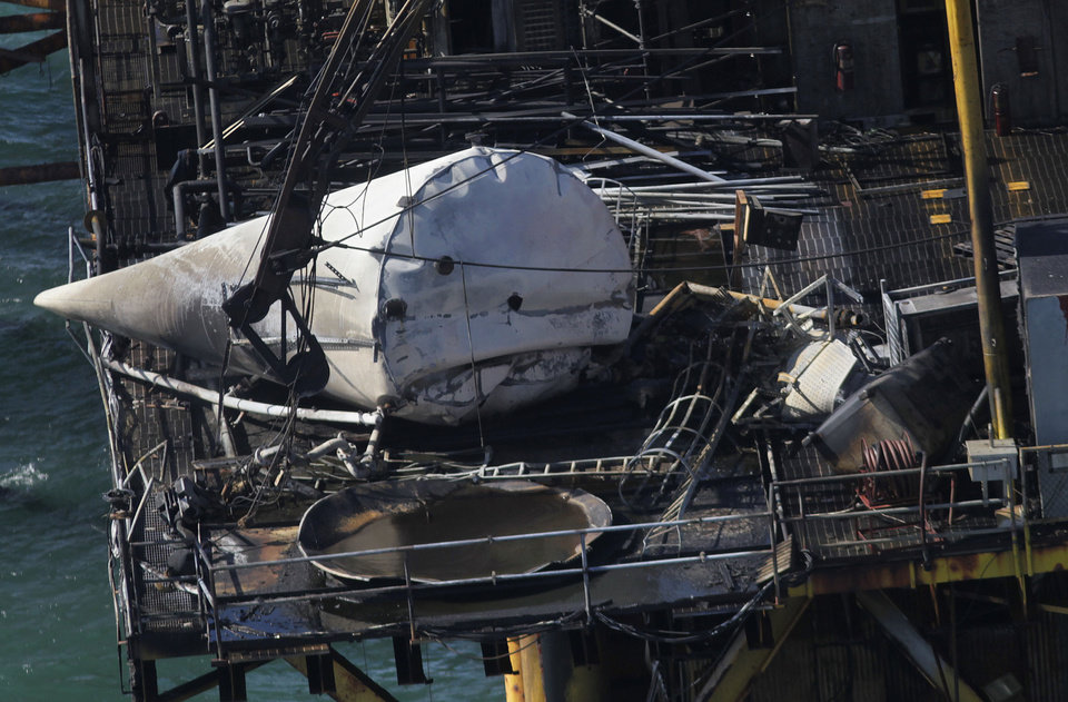 Photo -   This aerial photograph shows damage from an explosion and fire on an oil rig in the Gulf of Mexico, about 25 miles southeast of Grand Isle, La., Friday, Nov. 16, 2012. Four people were transported to a hospital with critical burns and two were missing. (AP Photo/Gerald Herbert)