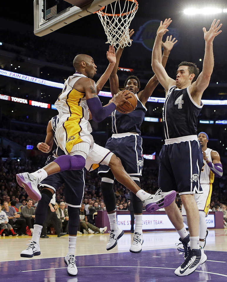 Photo - Los Angeles Lakers guard Kobe Bryant (24) passes as Oklahoma City Thunder center Hasheem Thabeet, center, and forward Nick Collison (4) defend in the first half of an NBA basketball game in Los Angeles, Sunday, Jan. 27, 2013. The Lakers won 105-96. (AP Photo/Reed Saxon)
