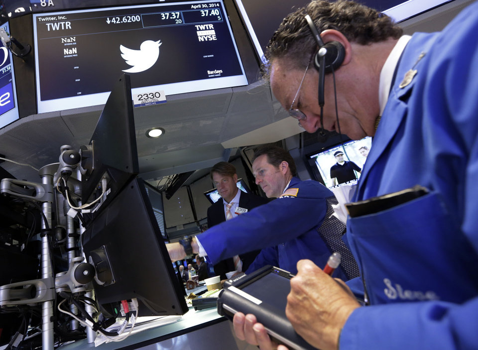 Trader Steven Kaplan, right, works at the post that handles Twitter, on the floor of the New York Stock Exchange, Wednesday, April 30, 2014.  Shares of Twitter dropped in morning trading Wednesday to their lowest point since the company went public in November. Investor concern remains over the short messaging service's ability to keep adding users and keep existing users engaged. (AP Photo)
