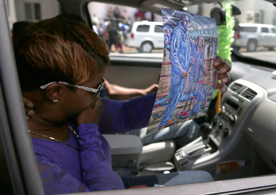 Photo - Lesley McSpadden, the mother of Michael Brown Jr., holds up an image of her with her son as she prepares to be driven away from a news conference outside the Old Courthouse, Tuesday, Aug. 12, 2014, in St. Louis. Michael Brown Jr., 18, who was unarmed, was shot to death Saturday by a Ferguson police officer while walking with a friend down the center of the street.(AP Photo/Jeff Roberson)