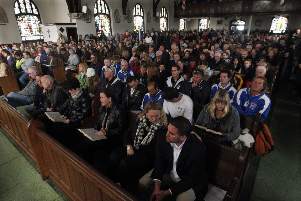 Photo -   Worshippers listen to a service by Diocese of Trenton American Roman Catholic Bishop David M. O'Connell at the Church of Saint Rose in Belmar, N.J., Sunday, Nov. 4, 2012. Many in the region who went through Monday's storm surge by Superstorm Sandy are still without power. (AP Photo/Mel Evans)