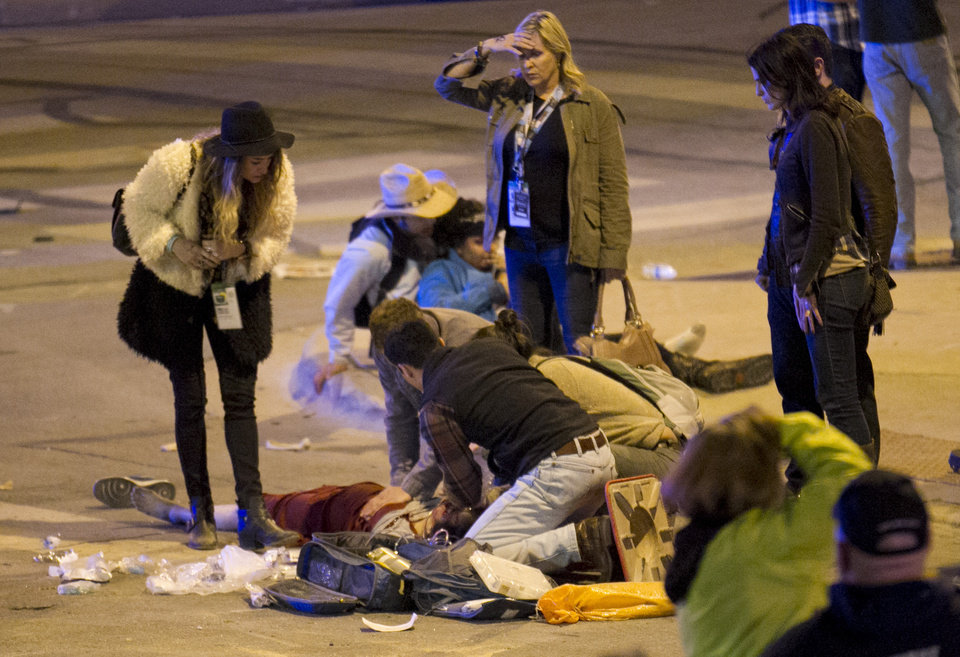 Photo - People perform CPR on a woman after she was struck by a vehicle on Red River Street in downtown Austin, Texas, at SXSW on Wednesday March 12, 2014. Her condition is unknown. Police say two people have died after a car drove through temporary barricades set up for the South By Southwest festival and struck a crowd of pedestrians.  (AP Photo/Austin American-Statesman, Jay Janner)