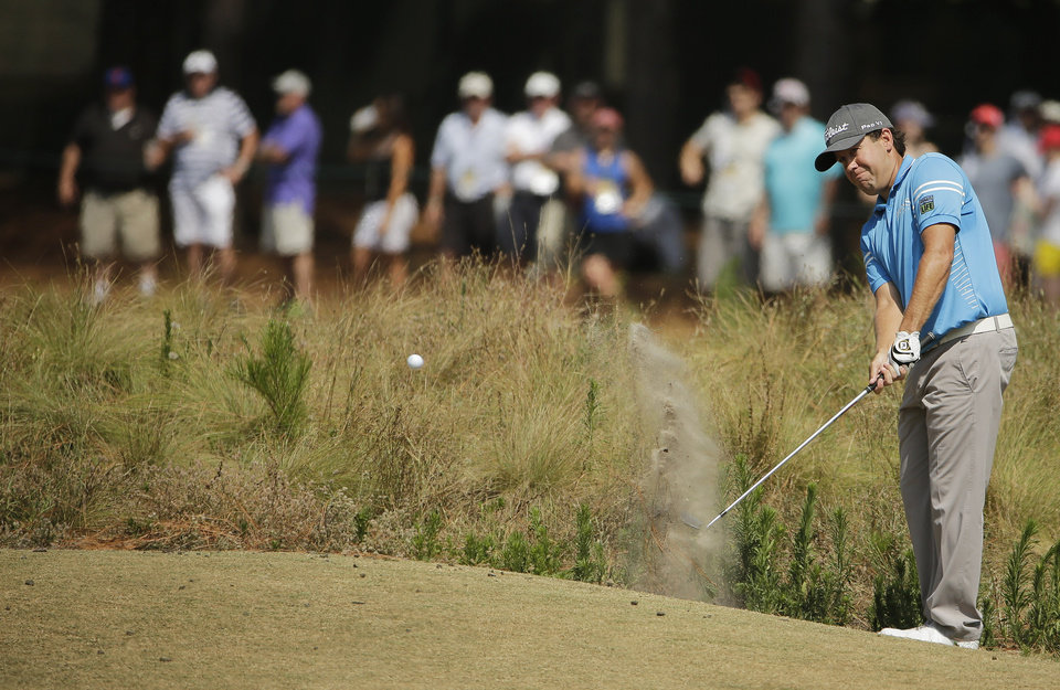 Photo - Erik Compton chips to the green on the seventh hole during the third round of the U.S. Open golf tournament in Pinehurst, N.C., Saturday, June 14, 2014. (AP Photo/Chuck Burton)