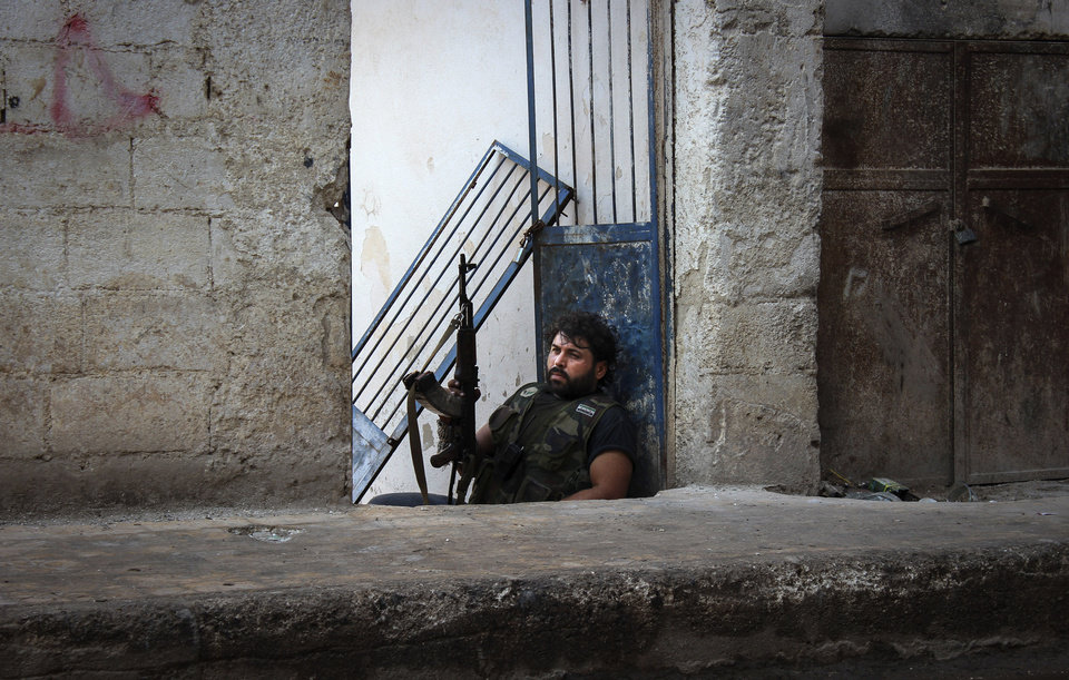 Photo -   In this Tuesday, Oct. 30, 2012 photo, Mustafa, a rebel from the town of Bennish, watches for a sniper firing down a street in the town of Harem, Syria. Despite two weeks of attacking a Roman-era citadel in which pro-Assad militia are dug in, the rebels failed to secure the town. (AP Photo/Mustafa Karali)