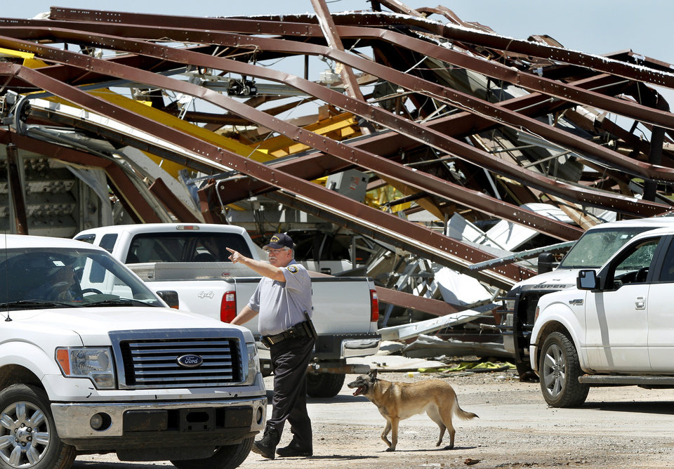 Photo - A police officer offers directions to a driver leaving this heavily damaged supply yard for Cactus Drilling Company on State Highway 66 in El Reno on Saturday, June 1, 2013. Employee David Stottemyre was working in the lot when the tornado took aim at the plant. Stottemyre ran inside the large supply storage building and took shelter as the tornado passed over, leaving the building in a twisted pile of steel and metal. He was not injured.  Photo  by Jim Beckel, The Oklahoman.