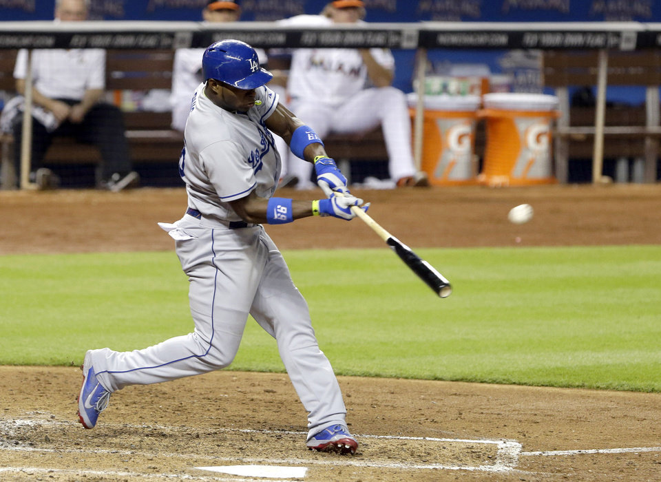 Photo - Los Angeles Dodgers' Yasiel Puig hits a three-run home run, also scoring Miguel Olivo and Dee Gordon, during the fourth inning of a baseball game against the Miami Marlins, Saturday, May 3, 2014, in Miami. (AP Photo/Wilfredo Lee)
