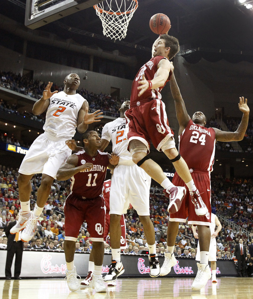 Photo - Oklahoma's Cade Davis (34) pulls in a rebound over Oklahoma's Obi Muonelo (2) in the second half of the college basketball game during the men's Big 12 Championship tournament at the Sprint Center on Wednesday, March 10, 2010, in Kansas City, Mo. Photo by Chris Landsberger, The Oklahoman