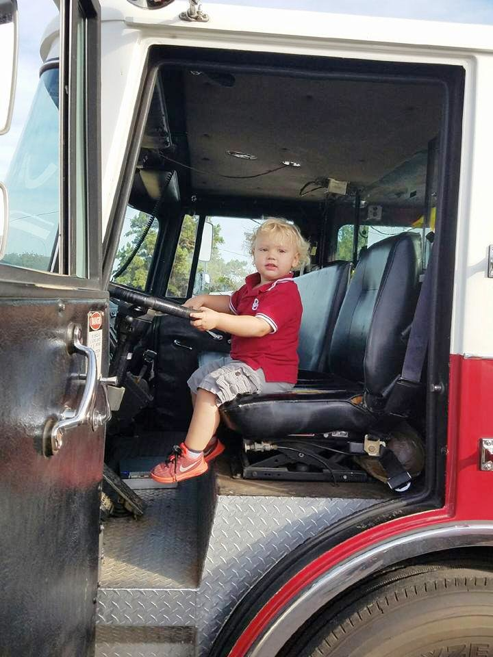 Photo -  Grayson Brooks sits in the driver's seat of a fire engine at Newalla Fire Department. [Photo provided]