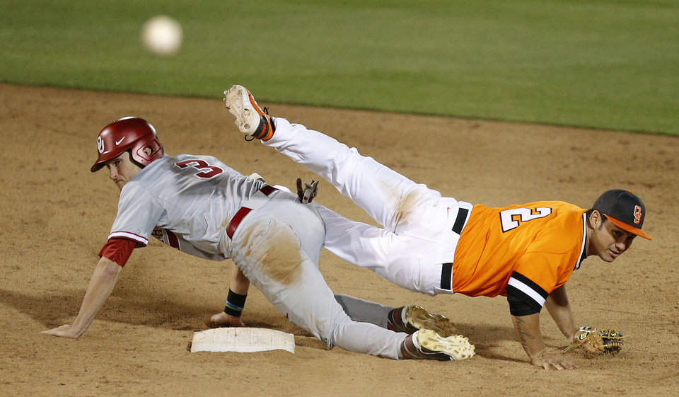 Photo - OSU's Tim Arakawa trips over OU's Craig Aikin after throwing from second to complete a double play in the 14h inning of a Bedlam baseball game between Oklahoma State University and the University of Oklahoma in Stillwater, Tuesday, April 15, 2014. Photo by Bryan Terry, The Oklahoman