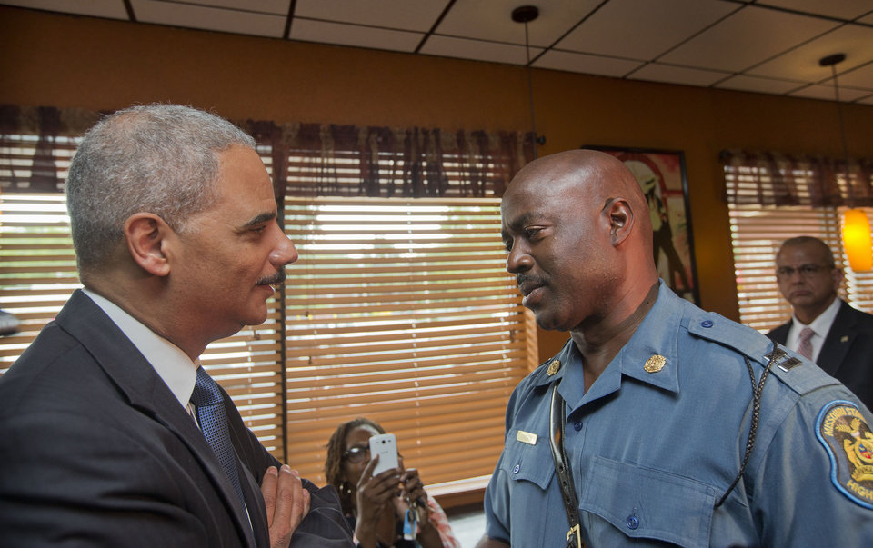 Photo - Attorney General Eric Holder speaks with Capt. Ron Johnson of the Missouri State Highway Patrol at Drake's Place Restaurant, Wednesday, Aug. 20, 2014, in Ferguson, Mo. Holder arrived in Missouri on Wednesday, a small group of protesters gathered outside the building where a grand jury could begin hearing evidence to determine whether a Ferguson police officer who shot 18-year-old Michael Brown should be charged in his death.   (AP Photo/Pablo Martinez Monsivais, Pool)