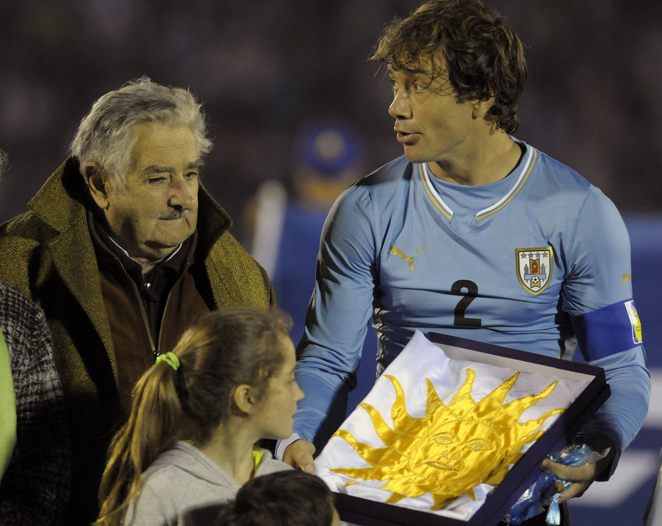FILE - In this June 4, 2014, file photo, Uruguay\'s President Jose Mujica, left, gives Uruguay\'s captain Diego Lugano the national flag before an international friendly soccer match against Slovenia in Montevideo, Uruguay. Uruguay\'s famously casual President is tossing some earthy expletives at FIFA as he welcomed Uruguay\'s team back from the World Cup oon Sunday June 29, over its four-month ban of Luis Suarez. Uruguayans overwhelmingly criticized FIFA\'s decision to ban Suarez from nine national team games and four months for biting an Italian defender. (AP Photo/Matilde Campodonico, File)