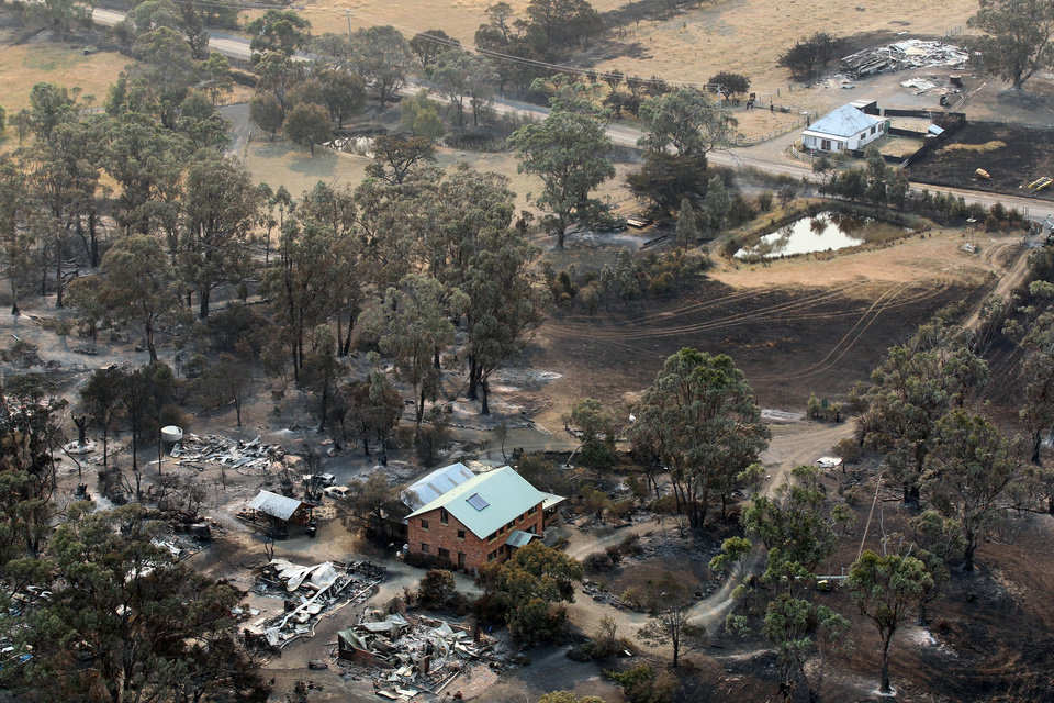Photo - A building sits among the charred remains of properties following a wildfire near Dunalley, east of the Tasmanian capital of Hobart, Australia, Saturday, Jan. 5, 2013.  Australian officials battled a series of wildfires amid scorching temperatures across the country on Saturday, with one blaze destroying dozens of homes in the island state of Tasmania. (AP Photo/Chris Kidd, Pool)