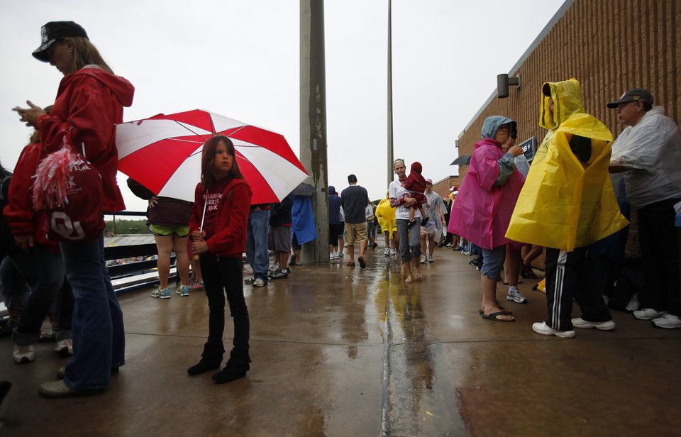 Alexis Gay, 6, of Washington, Okla., holds an umbrella at ASA Hall of Fame Stadium in Oklahoma City, Wednesday, June 6, 2012.  The Women's College World Series softball championship game was delayed due to rain.  Photo by Garett Fisbeck, The Oklahoman