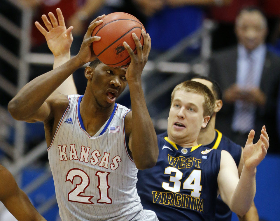 Photo - Kansas center Joel Embiid (21) rebounds against West Virginia forward Kevin Noreen (34) during the first half of an NCAA college basketball game in Lawrence, Kan., Saturday, Feb. 8, 2014. (AP Photo/Orlin Wagner)