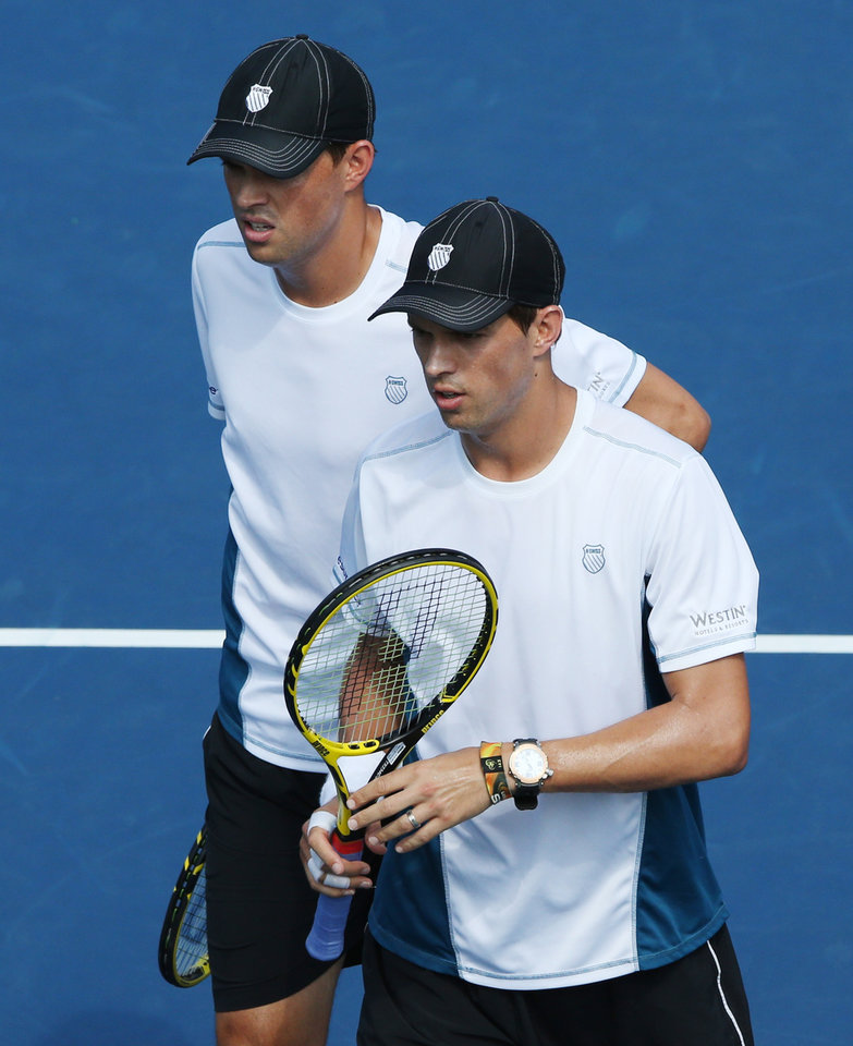 Photo - Bob Bryan, left, and Mike Bryan walk to their bench during a break in play against Bradley Klahn and Tim Smyczek, of the United States, during the third round of the 2014 U.S. Open tennis tournament, Friday, Aug. 29, 2014, in New York. (AP Photo/John Minchillo)