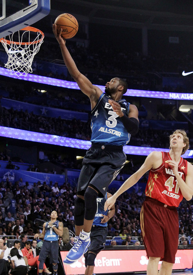 Eastern Conference's Dwyane Wade (3), of the Miami Heat, shoots a layup past Western Conference's Dirk Nowitzki (41), of the Dallas Mavericks, during the second half of the NBA All-Star basketball game, Sunday, Feb. 26, 2012, in Orlando, Fla. (AP Photo/Chris O'Meara) ORG XMIT: DOA140