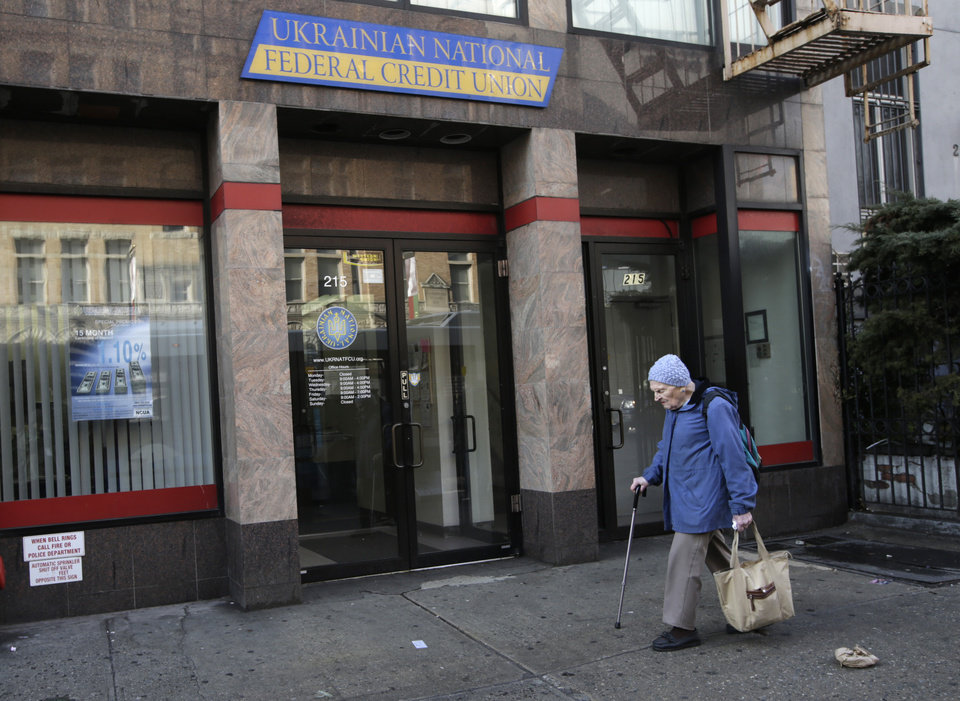Photo - A woman walks past the Ukrainian National Federal Credit Union, Wednesday, Feb. 19, 2014, in the Ukrainian neighborhood in Manhattan's East Village, New York.  Ukrainian-Americans expressed concern Wednesday after violent anti-government protests in Kiev, Ukraine, led to the deaths 26 people. (AP Photo/Kathy Willens)