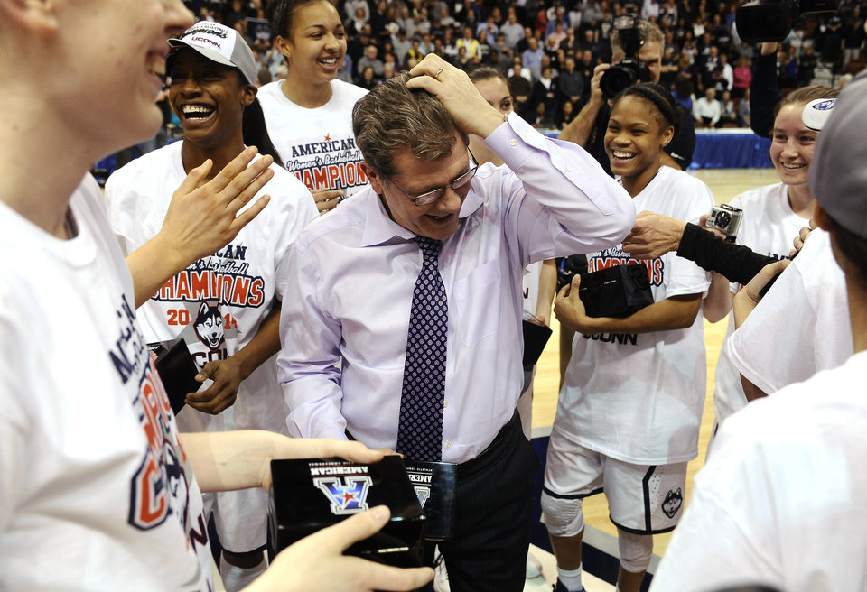 Photo - Connecticut head coach Geno Auriemma, center, fixes his hair after his team jokingly messed with it after winning the finals of the American Athletic Conference women's NCAA college basketball game against Louisville, Monday, March 10, 2014, in Uncasville, Conn. Connecticut won 72-52. (AP Photo/Jessica Hill)